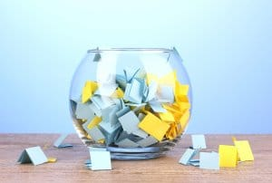 Pieces-of-paper-for-lottery-in-vase-on-wooden-table-on-blue-background